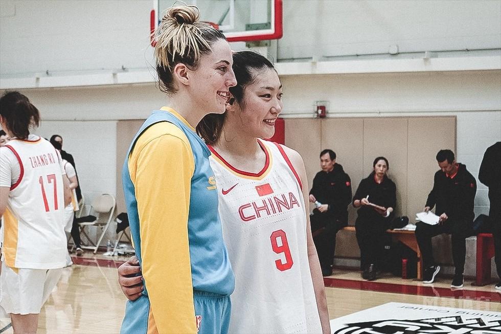 女篮姑娘们与对手合影,笑容灿烂